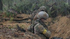 Οι στρατιώτες στην κάλυψη με τα όπλα αγώνα απολύονται στο καταφύγιο του δάσους, η στρατιωτική έννοια απόθεμα βίντεο