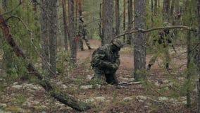 Οι στρατιώτες στην κάλυψη με τα όπλα αγώνα απολύονται στο καταφύγιο του δάσους, η στρατιωτική έννοια φιλμ μικρού μήκους
