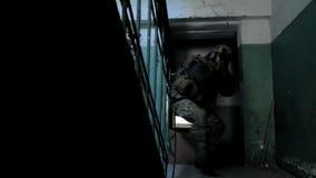Οι στρατιώτες στην κάλυψη με τα όπλα αγώνα γλιστρούν κατά μήκος των διαδρόμων του παλαιού κτηρίου, η στρατιωτική έννοια φιλμ μικρού μήκους