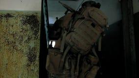 Οι στρατιώτες στην κάλυψη με τα όπλα αγώνα γλιστρούν κατά μήκος των διαδρόμων του παλαιού κτηρίου, η στρατιωτική έννοια απόθεμα βίντεο