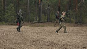Οι στρατιώτες στην κάλυψη με τα όπλα αγώνα κάνουν τον τρόπο τους έξω από το δάσος, συλλαμβάνοντας τον με στόχο, οι στρατιωτικοί φιλμ μικρού μήκους