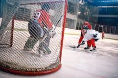 Οι στόχοι χόκεϋ, πυροβολούν τη σφαίρα και επιτίθενται στον τερματοφύλακας Στοκ εικόνες με δικαίωμα ελεύθερης χρήσης