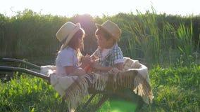 Οι συγκινήσεις των παιδιών, του μικρού παιδιού και του κοριτσιού τρώνε τα μήλα και έχουν τη διασκέδαση wheelbarrow με ένα καρό στ φιλμ μικρού μήκους
