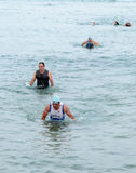 Οι συμμετέχοντες του ετήσιου triathlon τελειώνουν κολυμπούν στο Μ Στοκ Εικόνα