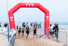 Οι συμμετέχοντες του ετήσιου triathlon τελειώνουν κολυμπούν στο Μ Στοκ Φωτογραφίες