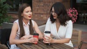 Οι συνάδελφοι μιλούν πέρα από ένα φλιτζάνι του καφέ επιχειρησιακές γυναίκες που κάθονται σε έναν θερινούς καφέ και μια ομιλία φιλμ μικρού μήκους