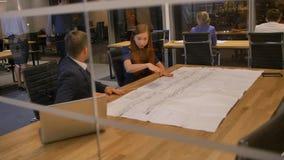 Οι συνάδελφοι στον πίνακα φαίνονται το έγγραφο σχεδίων και η ομιλία απόθεμα βίντεο