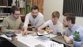 Οι συνάδελφοι συζητούν τη συνεδρίαση σχεδίου στον πίνακα στην αρχή φιλμ μικρού μήκους
