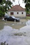 Οι συνέπειες της πλημμύρας, αυτοκίνητο μπροστά από το πλημμυρισμένο σπίτι Στοκ Εικόνες