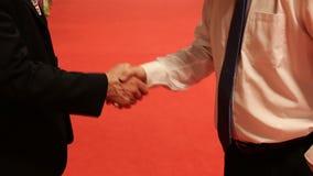 Οι συνέταιροι συναντούν και τινάζουν τα χέρια στο κόκκινο απόθεμα βίντεο