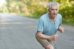 Οι συνταξιούχες βέβαιες αρσενικές στάσεις στην έναρξη, έτοιμη να συμμετέχει στα αθλητικά comeptitions, ακούνε μουσική με τα ακουσ Στοκ Εικόνες