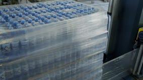 Οι συσκευασίες με το εμφιαλωμένο νερό συσκευάζονται στο πολυαιθυλένιο αυτόματα απόθεμα βίντεο