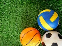 Οι σφαίρες για το ποδόσφαιρο, την καλαθοσφαίριση και την πετοσφαίριση βρίσκονται στην πράσινη χλόη Στοκ εικόνα με δικαίωμα ελεύθερης χρήσης