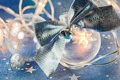 Οι σφαίρες γυαλιού χριστουγεννιάτικων δέντρων με το ασημένιο τόξο στο μπλε ακτινοβολούν backg Στοκ φωτογραφία με δικαίωμα ελεύθερης χρήσης