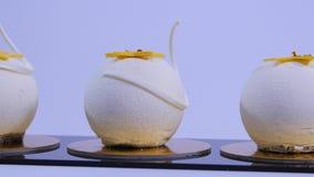 Οι σφαίρες κέικ βελούδου με τη ζάχαρη ψεκάζουν Άσπρα, σφαίρα-διαμορφωμένα κέικ Διακοσμητικά άσπρα κέικ απόθεμα βίντεο