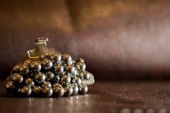 Οι σφαίρες μετάλλων από το ρουλεμάν είναι κολλημένες στο μαγνήτη νεοδύμιου, ο οποίος βρίσκεται στην επιφάνεια δέρματος του καφετι Στοκ φωτογραφία με δικαίωμα ελεύθερης χρήσης