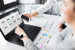 Οι σχεδιαστές Ιστού εργάζονται στο ενδιάμεσο με τον χρήστη smartphone στοκ φωτογραφία