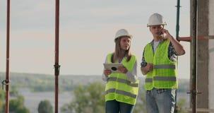 Οι σχεδιαστές μηχανικών στέκονται στη στέγη του κτηρίου κάτω από την οικοδόμηση και συζητούν το σχέδιο και την πρόοδο απόθεμα βίντεο