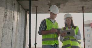 Οι σχεδιαστές μηχανικών στέκονται στη στέγη του κτηρίου κάτω από την οικοδόμηση και συζητούν το σχέδιο και την πρόοδο φιλμ μικρού μήκους