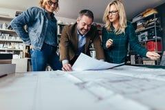 Οι σχεδιαστές οριστικοποιούν ένα σχέδιο κατασκευής κατοικίας Στοκ Φωτογραφία