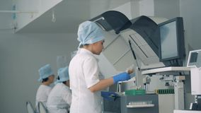 Οι σωλήνες δοκιμής παίρνουν επανεντοπισμένοι στη βιοχημική συσκευή ανάλυσης από έναν εργαστηριακό εργαζόμενο φιλμ μικρού μήκους
