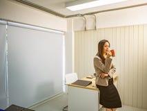 Οι σύγχρονες επιχειρησιακές γυναίκες κρατούν το φλυτζάνι ή την κούπα καφέ της στοκ φωτογραφίες