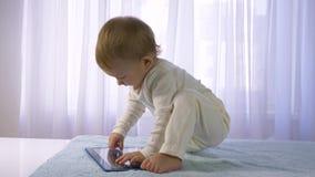Οι σύγχρονες τεχνολογίες στην ανάπτυξη παιδιών, συμπαθητικό ευτυχές νήπιο παίζονται με την ταμπλέτα στο φωτεινό δωμάτιο απόθεμα βίντεο