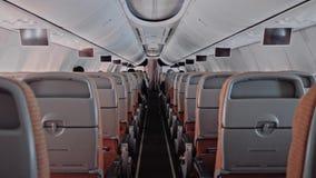 Οι σύγχρονοι μεγάλοι άνθρωποι καμπινών επιβατών επιβατηγών αεροσκαφών άποψης πίσω πλευρών στηρίζονται και προσέχουν τη TV την πτή απόθεμα βίντεο