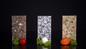 Οι σύγχρονοι μετρητές κουζινών έκαναν από την πέτρα γρανίτη, μαρμάρου και χαλαζία που διακοσμήθηκε με τα τρόφιμα Countertop κουζι Στοκ Εικόνες