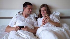Οι σύζυγοι βρίσκονται στο κρεβάτι και εξετάζουν το smartphone φιλμ μικρού μήκους