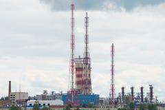Οι τέσσερις σωλήνες του σταθμού θερμότητας καπνίζουν νωρίς το πρωί ενάντια στο μπλε ουρανό στοκ φωτογραφία