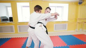 οι τέχνες κατευθύνουν Δύο άτομα που εκπαιδεύουν τις δεξιότητες aikido τους Parries το χτύπημα και ρίψη του αντιπάλου στο πάτωμα απόθεμα βίντεο