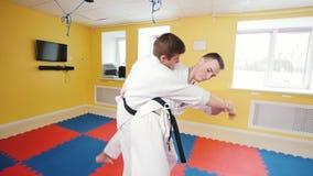 οι τέχνες κατευθύνουν Δύο αθλητικά άτομα που εκπαιδεύουν τις δεξιότητες aikido τους στο φωτεινό στούντιο Parries το χτύπημα και ρ φιλμ μικρού μήκους