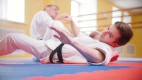 οι τέχνες κατευθύνουν Δύο αθλητικά άτομα που εκπαιδεύουν τις δεξιότητες aikido τους στο στούντιο Να βρεθεί στο πάτωμα και χτύπημα απόθεμα βίντεο