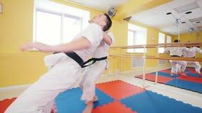οι τέχνες κατευθύνουν Δύο αθλητικά άτομα που εκπαιδεύουν τις δεξιότητες aikido τους στο στούντιο Parries το χτύπημα και ρίψη του  φιλμ μικρού μήκους