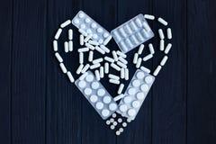 Οι ταμπλέτες, κάψες χαπιών, χάπι βγάζουν φουσκ'αλες στη μορφή της καρδιάς στο Μαύρο Στοκ Εικόνες