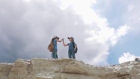Οι ταξιδιώτες παιδιών με τα σακίδια πλάτης δίνουν σε μεταξύ τους υψηλά πέντε απόθεμα βίντεο