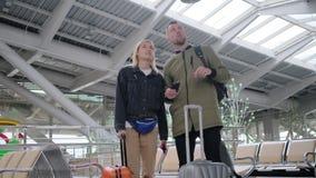 Οι ταξιδιώτες στέκονται μέσα στη μεγάλη αίθουσα αναμονής του αερολιμένα, του άνδρα και της γυναίκας απόθεμα βίντεο