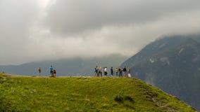 Οι ταξιδιώτες στέκονται σε ένα βουνό και εξετάζουν γύρω τη φύση στοκ φωτογραφία με δικαίωμα ελεύθερης χρήσης