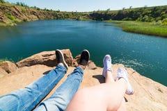 Οι ταξιδιώτες συνδέουν στα αθλητικά παπούτσια σε ένα βουνό κοντά σε έναν ποταμό στο υπόβαθρο της φύσης Άνδρας και γυναίκα Ένα ζεύ στοκ εικόνες με δικαίωμα ελεύθερης χρήσης