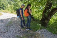 Οι ταξιδιώτες ταξιδεύουν στο δρόμο στα βουνά πηγαίνουν από κοινού ενάντια ανασκόπησης μπλε σύννεφων πεδίων άσπρο σε wispy ουρανού Στοκ Εικόνες
