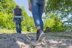 Οι ταξιδιώτες ταξιδεύουν στο δρόμο στα βουνά πηγαίνουν από κοινού ενάντια ανασκόπησης μπλε σύννεφων πεδίων άσπρο σε wispy ουρανού Στοκ εικόνα με δικαίωμα ελεύθερης χρήσης