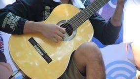 Οι ταϊλανδικοί λαοί παιδιών που παίζουν την ακουστική κιθάρα για παρουσιάζουν ταξιδιώτες απόθεμα βίντεο