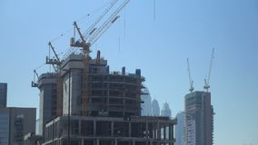 Οι τεράστιοι γερανοί οικοδόμησης είναι στο ατελές κτήριο στη μεγάλη σύγχρονη πόλη, στη θερινή ημέρα φιλμ μικρού μήκους