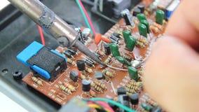 Οι τεχνικοί χρησιμοποιούν έναν συγκολλώντας σίδηρο για την επισκευή ηλεκτρονική του πίνακα κυκλωμάτων υπολογιστών απόθεμα βίντεο