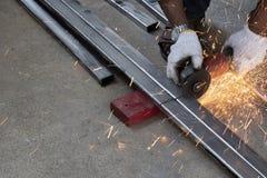 Οι τεχνικοί χρησιμοποιούν τις αλέθοντας μηχανές για να κόψουν τους σωλήνες χάλυβα στοκ εικόνα