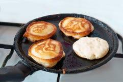 Οι τηγανίτες είναι τηγανισμένες σε ένα τηγανίζοντας τηγάνι, τέσσερις τηγανίτες είναι μαγειρευμένες στο πετρέλαιο σε ένα τηγανίζον Στοκ εικόνες με δικαίωμα ελεύθερης χρήσης