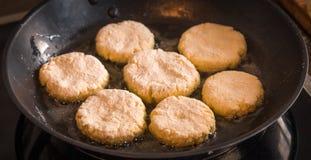 Οι τηγανίτες είναι τηγανισμένες σε ένα τηγανίζοντας τηγάνι Στοκ Εικόνες