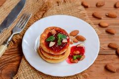 Οι τηγανισμένες τηγανίτες τυριών εξοχικών σπιτιών με το μούρο φράσσουν, αμύγδαλα και μέντα σε ένα άσπρο πιάτο Συνταγή Syrniki Χαμ Στοκ φωτογραφία με δικαίωμα ελεύθερης χρήσης