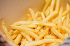 Οι τηγανιτές πατάτες εξυπηρετούν στο κιβώτιο εγγράφου για το υπόβαθρο ή το κείμενο γρήγορου φαγητού Στοκ εικόνα με δικαίωμα ελεύθερης χρήσης